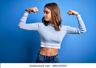 Young beautiful blonde girl wearing casual sweater standing over blue isolated background showing arms muscles smiling proud. Fitness concept.