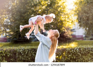 Young beautiful blonde mother with her baby girl laughing together and playing in green park outdoors at sunny day