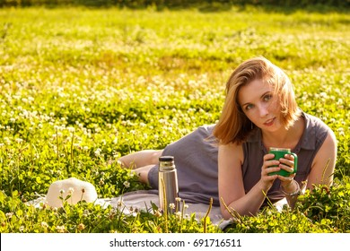 young beautiful blonde on a picnic with a Cup of hot tea on a background of green grass