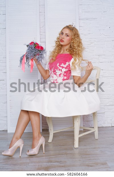 young beautiful blonde princess wearing a crown and a short dress on a white background