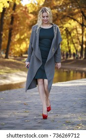 Young beautiful blonde sexy woman in gray coat walking on the autumn park