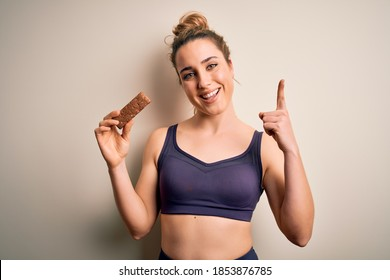 Young beautiful blonde sportswoman wearing sportswear holding energetic protein bar surprised with an idea or question pointing finger with happy face, number one