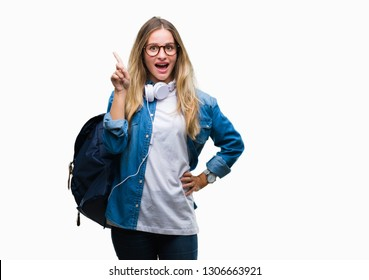 2c1082e3ef972 Young beautiful blonde student woman wearing headphones and glasses over  isolated background pointing finger up with