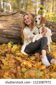 Young beautiful blonde walking with dog in the autumn park. Autumn sunny day.