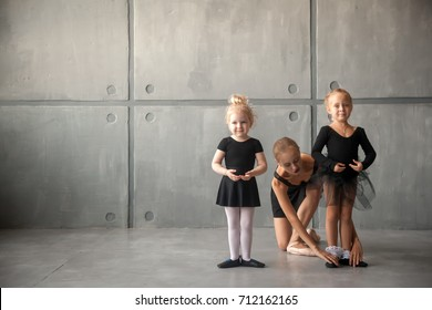 Young beautiful blonde woman ballet dancer in black dress, bulging pantyhose and pointe shoes tying pointes to small fair-haired girls ballerines in black dresses in a dark dance studio