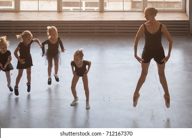 young beautiful blonde woman ballet dancer in black dress, bulging pantyhose and pointe shoes teaches small fair-haired girls ballerinas in black dresses to jump and dance Russian ballet in a studio