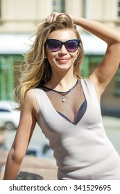 Young beautiful blonde woman in beige short dress posing outdoors in sunny weather