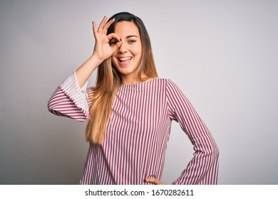 Young beautiful blonde woman with blue eyes wearing stiped t-shirt over white background doing ok gesture with hand smiling, eye looking through fingers with happy face.