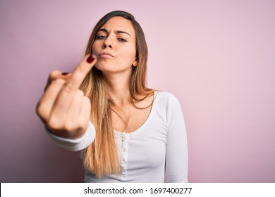 Young beautiful blonde woman with blue eyes wearing white t-shirt over pink background Showing middle finger, impolite and rude expression