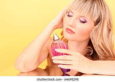 Young beautiful blonde  woman with bottle of perfume  on yellow background