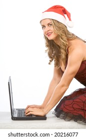 Young beautiful blonde woman in Christmas hat standing on knees with her hands on keyboard of portable notebook computer