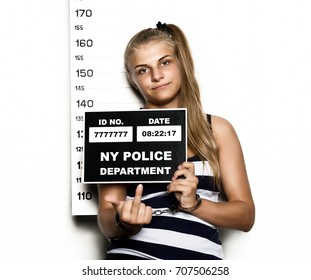 Young beautiful blonde woman Criminal Mug Shots. imprisoned girl shows middle finger