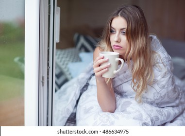 Young beautiful blonde woman with cup of coffee sitting home on the bed covered with duvet by the window. Lazy morning day off concept