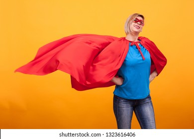 Young and beautiful blonde woman dressed like superheroine with red cape in the air. Red mask. Woman super powers. Red mask.