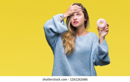 Young beautiful blonde woman eating sweet donut over isolated background stressed with hand on head, shocked with shame and surprise face, angry and frustrated. Fear and upset for mistake.