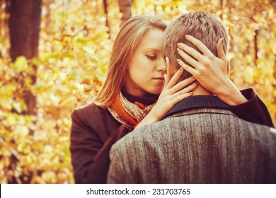 Young beautiful blonde woman embraces a man in autumn park, tenderness scene