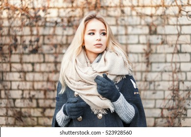 Young beautiful blonde woman with fashionable warm scarf near a brick wall