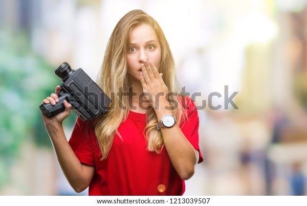 Young beautiful blonde woman filming using vintage camera over isolated background cover mouth with hand shocked with shame for mistake, expression of fear, scared in silence, secret concept
