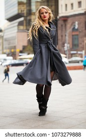 Young beautiful blonde woman in gray coat walking on the autumn street of Moscow