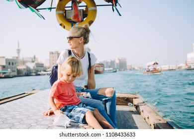 Young beautiful blonde woman and her cute little son sitting at pier