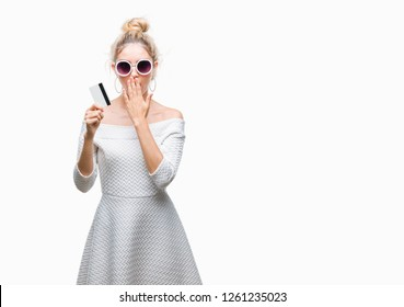 Young beautiful blonde woman holding credit card over isolated background cover mouth with hand shocked with shame for mistake, expression of fear, scared in silence, secret concept