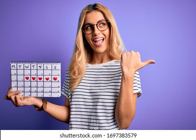 Young beautiful blonde woman holding period calendar to control menstrual cycle pointing and showing with thumb up to the side with happy face smiling