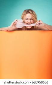 Young beautiful blonde woman holding roll of toilet paper with smiling surprised face in studio on turquoise background and orange sheet