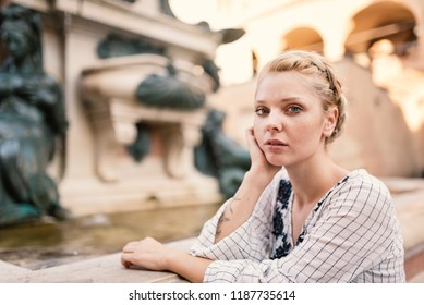 Young beautiful blonde woman intimate portrait outdoors in Bologna, Italy. Natual flare.