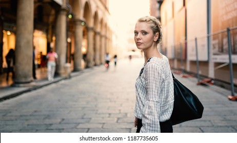Young beautiful blonde woman lifestyle portrait outdoors in Bologna, Italy. Natual flare.