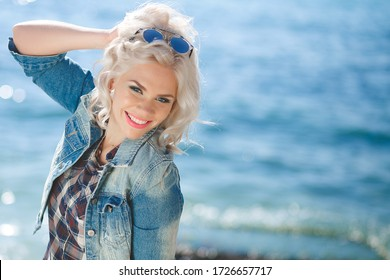 Young beautiful blonde woman near the sea