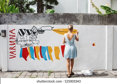 Young beautiful blonde woman painting the wall, street art in process, street artist - painter