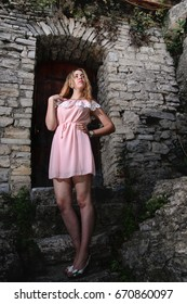 Young beautiful blonde woman in pink dress against the background of a stone old wall with a small vintage door and with ivy.