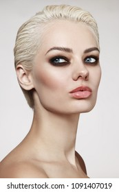 Young beautiful blonde woman with pixie hair cut and smoky eye make-up
