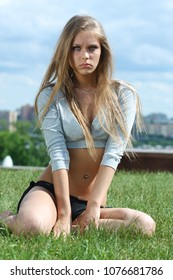 Young beautiful blonde woman posing while sitting on the green grass against the background of the city of Moscow
