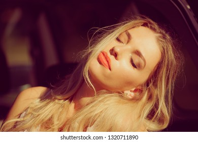 Young beautiful blonde woman relaxing in car during summer vacations trip. Moment of chillout while traveling.