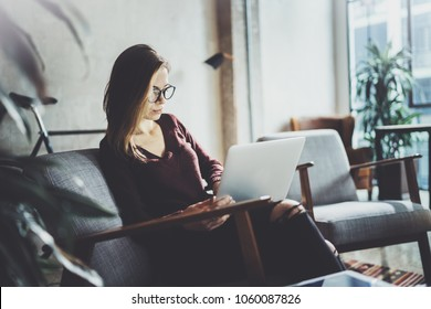 Young beautiful blonde woman sitting at the comfortable armchair and using laptop computer.Working process at coworking studio.Panoramic windows on blurred background