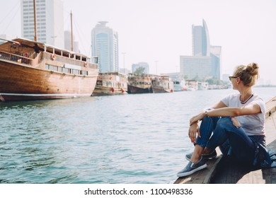 Young beautiful blonde woman sitting at pier and looking at sea