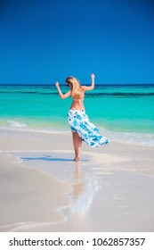 Young beautiful blonde woman with slim tan body in bikini swimwear and long floral skirt on white sand Maldive beach