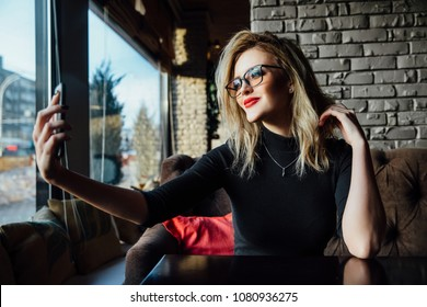 Young beautiful blonde woman taking a selfie in coffee shop. Hipster, red lips, glasses. Against the background of a brick stylish design wall.