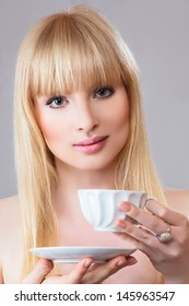 Young beautiful blonde woman with tea cup against light gray background