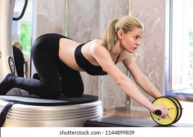 Young beautiful blonde woman is training abs with roller for abs at home.