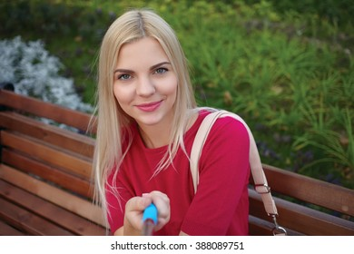 Young beautiful blonde woman with trendy bright makeup in fuchsia blouse doing a selfie portraits sitting on the park bench
