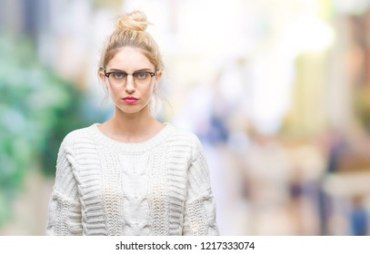 Young beautiful blonde woman wearing glasses over isolated background with serious expression on face. Simple and natural looking at the camera.