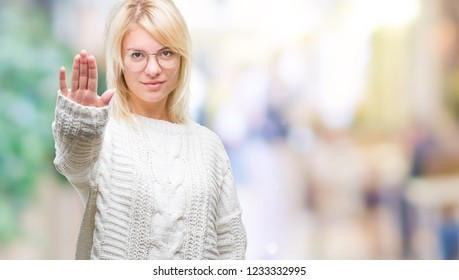 Young beautiful blonde woman wearing winter sweater and glasses over isolated background doing stop sing with palm of the hand. Warning expression with negative and serious gesture on the face.