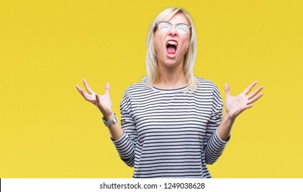 Young beautiful blonde woman wearing glasses over isolated background crazy and mad shouting and yelling with aggressive expression and arms raised. Frustration concept.