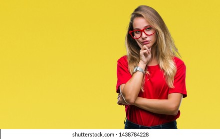 Young beautiful blonde woman wearing glasses over isolated background thinking looking tired and bored with depression problems with crossed arms.
