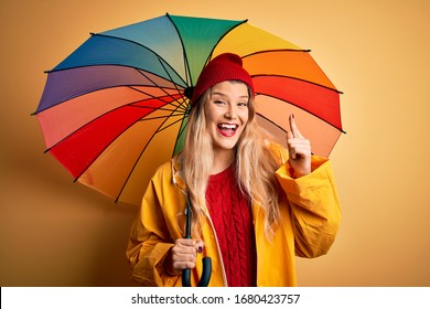 Young beautiful blonde woman wearing raincoat and wool cap holding colorful umbrella very happy pointing with hand and finger