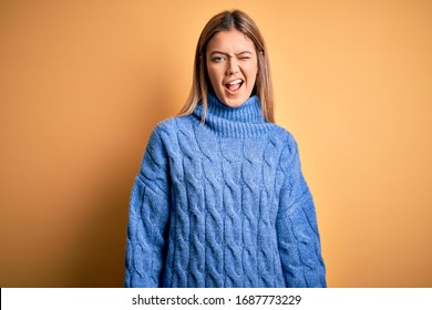 Young beautiful blonde woman wearing turtleneck sweater over yellow isolated background winking looking at the camera with sexy expression, cheerful and happy face.