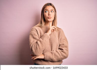 Young beautiful blonde woman wearing winter wool sweater over pink isolated background Thinking concentrated about doubt with finger on chin and looking up wondering