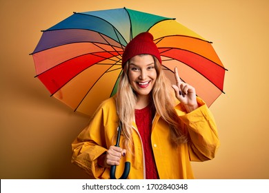 Young beautiful blonde woman wearing raincoat and wool cap holding colorful umbrella surprised with an idea or question pointing finger with happy face, number one